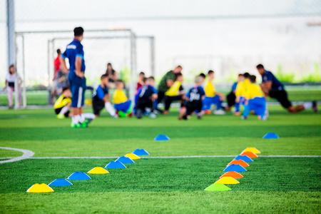 Los marcadores de cono son equipos de entrenamiento de fútbol en césped artificial verde con fondo de entrenamiento de jugadores de niños borrosos. Material para la clase de entrenamiento de la academia de fútbol. Foto de archivo