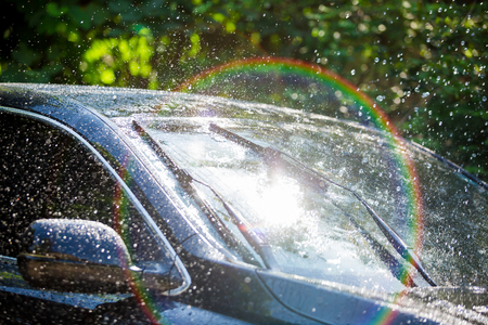Car windshield with rain drops and frameless wiper blade closeup Stock Photo