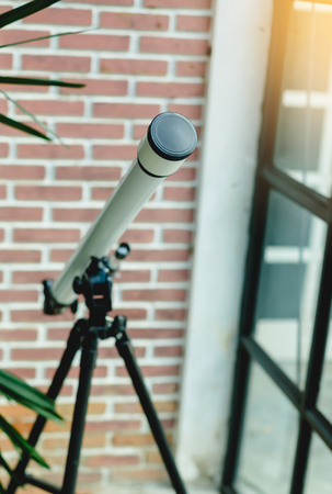 white telescope with red brick wall Stok Fotoğraf