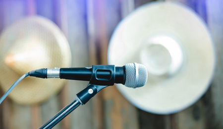 microphone on a stand up comedy stage with blurry wooden wall and straw hat Banque d'images - 115949138