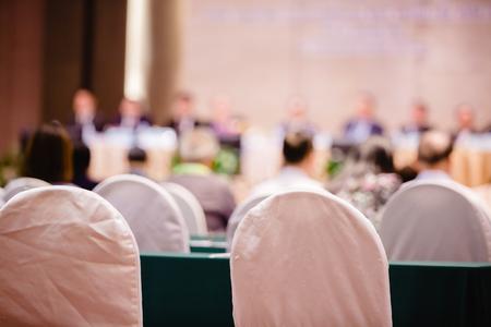 Sedia in tessuto bianco con sfocatura dell'auditorium per assemblea degli azionisti o seminario.