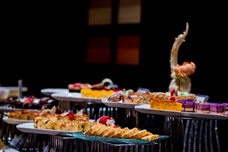 Different delicious desserts and cakes on the buffet table with selective focus