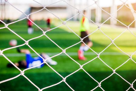 Mesh of goal with blurry of soccer goalkeeper and soccer players. Soccer ball training in academy. Archivio Fotografico