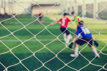 Malla de portería con borrosa de portero de fútbol y jugadores de fútbol. Entrenamiento de balón de fútbol en academia.