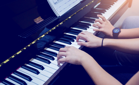 Selective focus to picture of young woman teaching a boy to play the piano with music notation. Four hands from two people playing piano. There are musical instrument for learning music.