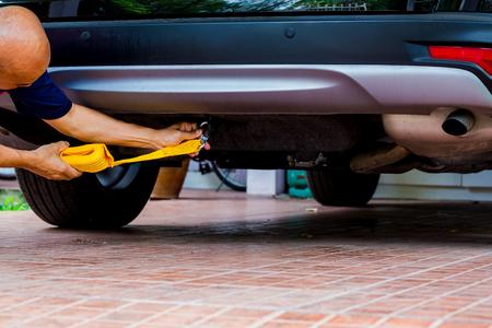 Hände des Mannes, der gelbes Auto-Abschleppband mit Auto hält Abschleppen des Autos. Abschleppseil