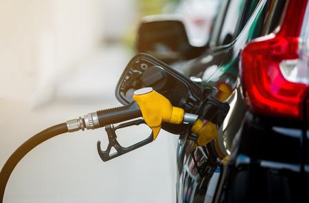 Hand die de witte pick-up bijvult met brandstof bij het benzinestation. Olie en gas energie.
