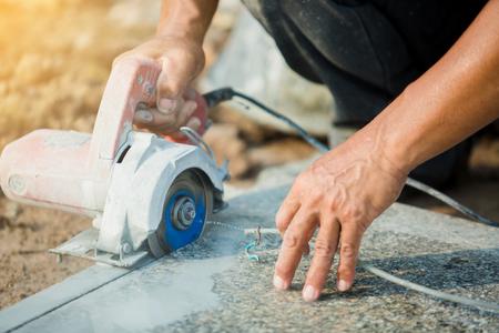 Arbeiter schneiden Granitstein mit einem elektrischen Diamantsägeblatt und verwenden Wasser, um Staub und Hitze auf einer Baustelle zu vermeiden