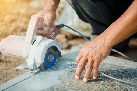 worker cutting granite stone with an diamond electric saw blade and use water to prevent dust and heat at a construction site 免版税图像