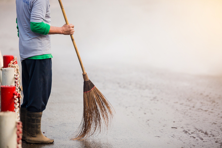 staff cleaning city street with broom tool and water spray