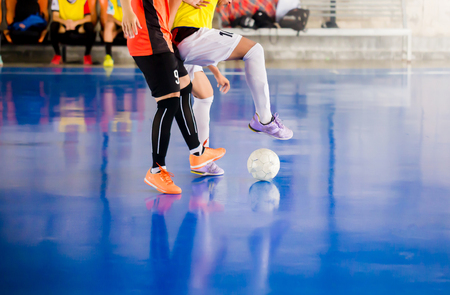 Futsal player  trap and control the ball for shoot to goal. Soccer players fighting each other by kicking the ball. Indoor soccer sports hall. Football futsal player, ball, futsal floor. 写真素材