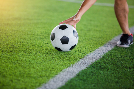 soccer player get the ball or placing the ball to free kick or penalty kick during match on artificial turf.