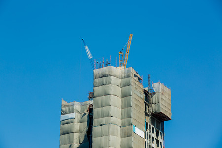Building crane and buildings under construction with blue sky background.