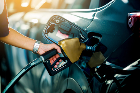 Hand refilling the car with fuel at the refuel station, 
