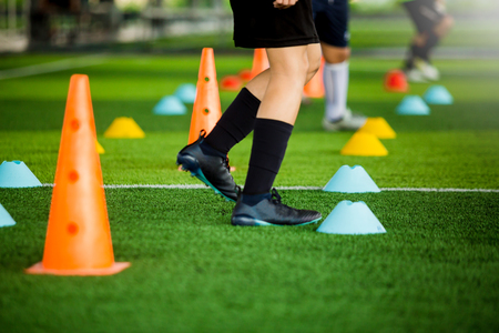 kid soccer team jogging between yellow and blue marker cones for football training on green artificial turf, It is activity on holiday in soccer academy.