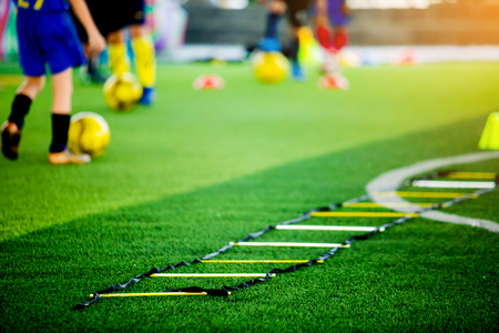selective focus to ladder drills on green artificial turf with blurry coach and kid soccer are training, blurry kid soccer jogging between marker cones and control ball with soccer equipment in soccer academy.