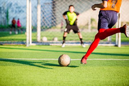 giocatore di calcio corre per sparare la palla al calcio di rigore verso la porta con sfondo sfocato del portiere, concetto di obiettivi e protezione