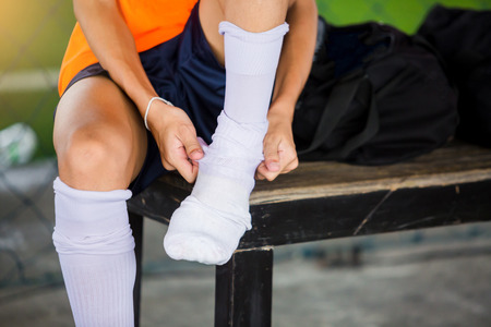 Soccer player is sitting and putting white sport sock before training football.