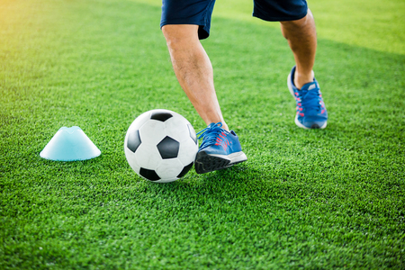 soccer player put blue sport shoes to jogging with trap and control football between cone markers for football training.