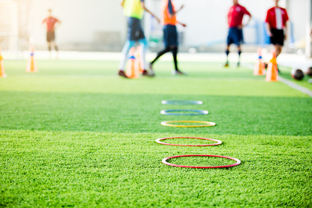 selective focus to ring ladder marker and cone are soccer training equipment on green artificial turf with blurry kid players training background. material for training class of football academy.