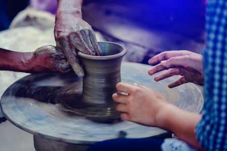 Making it together. close-up to hands of potter teacher and child. potter teaching child to make ceramic pot on the pottery wheel.