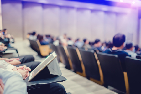 Blurry of auditorium for shareholders meeting or seminar event, many business people play tablet and smartphone on the conference for meeting information