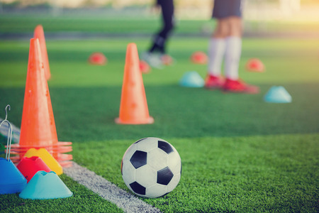 football and soccer training equipment on green artificial turf with blurry of soccer players training. Soccer Academy.