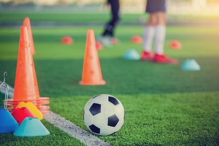 Fußball- und Fußballtrainingsgeräte auf grünem Kunstrasen mit verschwommenem Fußballtraining. Fußball-Akademie. Standard-Bild