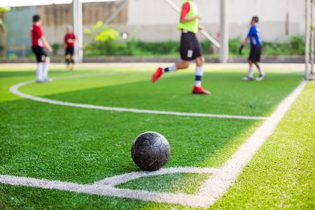 Fußball auf grünem Kunstrasen an der Ecke des Fußballplatzes mit verschwommenem Spielerhintergrund, Fußball an der Ecke für Eckstoß mit verschwommenen Kinderfußballspielern, Fußballtraining oder Fußballspiel.