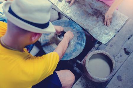 poterie, atelier, concept d'art céramique - gros plan sur des mains masculines sculptent un nouvel ustensile avec des outils et de l'eau, les doigts de l'homme travaillent avec un tour de potier et de l'argile réfractaire brute, à Ko Kret, Thaïlande