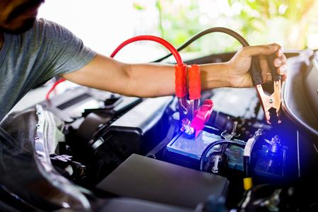 Selektive Fokushände laden die Autobatterie mit Strom über Kabel von einem anderen Auto auf, zuerst die Anode anschließen, dann die Batterie mit dem negativen Anschluss anschließen, Energieübertragungskonzept.