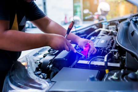 blurry of male mechanic changing car battery, mechanic engineer fixing car battery with delivery service on road or home, the concepts of car maintenance services in every location