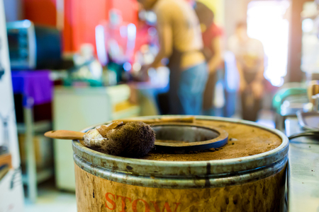 brush on wooden bucket of ground coffee from coffee machine with blurry staff at bar counter in restaurant or cafe background. Stockfoto