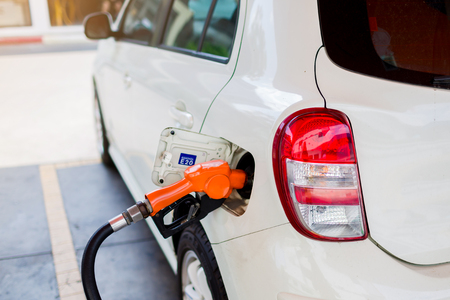Hand refilling the white car with fuel at the gas station. Oil and gas energy. Stock Photo