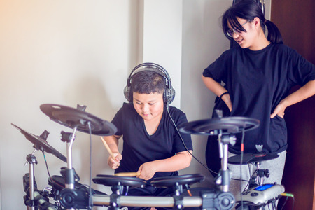 Asian girl and boy put black tshirt and headphone learning and play electronic drum with wooden drumsticks in home, smile and happy time in family.