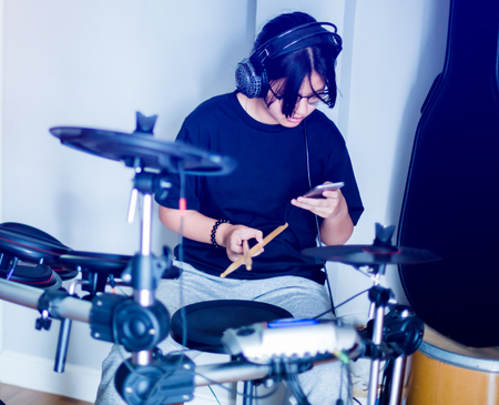 Young girl playing smartphone and electronic drum, Asian girl put black tshirt and headphone learning and play electronic drum with smart phone and wooden drumsticks in music room Фото со стока - 124095684