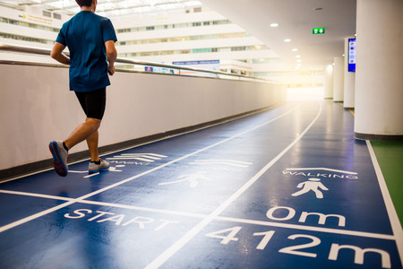 runner is running on blue running track in grand office building for employees to exercise and relax, Startup concept, Progress concept, Goal creation concept 写真素材