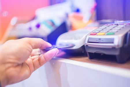 Carta di credito inserita a mano Nello slot del lettore di carte di credito, pagamento con carta di credito, acquisto e vendita di prodotti e servizi, concetto di pagamento senza contanti, messa a fuoco selettiva.
