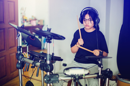 Asian girl put black tshirt and headphone learning and play electronic drum with wooden drumsticks in home, smile and happy time in family.