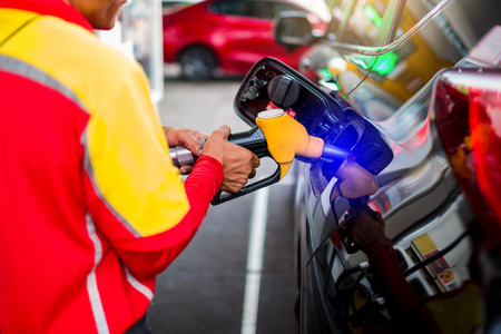 staff with Hand refilling the car with fuel at the gas station. Stock Photo