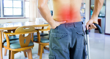 man with walking stick and terrible backache in home