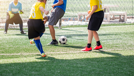 selective to kid soccer player and coach are training and fighting to shoot ball and charges kid goalkeeper. Asian boy soccer player in football academy.