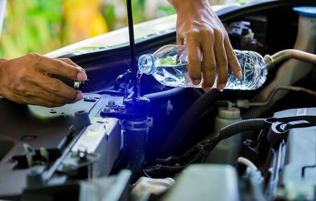 manos de mecánico Verifique el agua en el radiador del automóvil y agregue agua al radiador del automóvil, Servicio y mantenimiento de automóviles o vehículos, enfoque selectivo. Foto de archivo