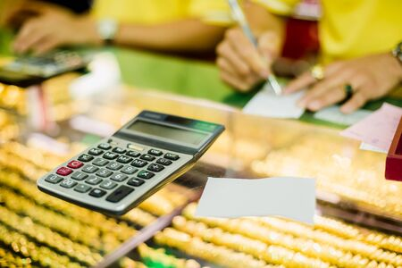 the calculator to calculate the purchase of gold jewelry with blurry sale staff writing on ticket in the gold shop. Banque d'images