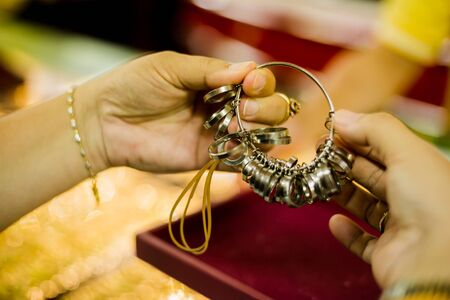 Women customers are measuring finger size with a ring of size to choose to buy gold van jewelry in gold shop. Yaowarat gold shop, Thailand.