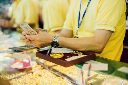 mise au point sélective sur le personnel compte les billets de banque, les clients achètent des bijoux en or dans le magasin d'or de Yaowarat, Bangkok, Thaïlande. Banque d'images