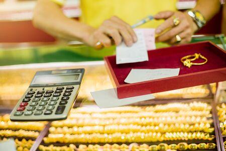 der Rechner, um den Kauf von Goldschmuck mit Verkauf verschwommenes Personal zu berechnen, das Ticket im Goldshop hält.