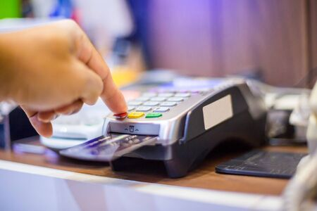 Hand put credit card In slot and press the button of credit card reader, credit card payment, buy and sell products & service, the concept of payment without cash, selective focus.