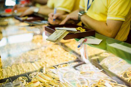 mise au point sélective sur les billets de banque et le personnel avec de vieux bijoux, les clients achètent des bijoux en or dans le magasin d'or de Yaowarat, Bangkok, Thaïlande.