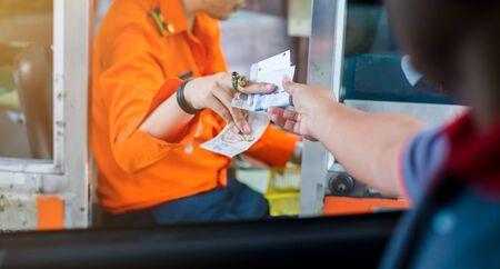 Mise au point sélective pour le conducteur payer pour l'autoroute. L'homme paie de l'argent à un caissier pour une entrée d'autoroute à péage. Péage express à la main sur la route. payer de manière expresse.